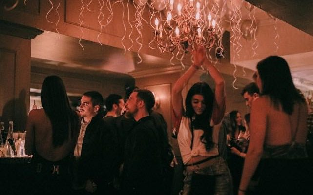 Young woman dances under the chandelier with lots of balloons at Mayfair cocktail bar