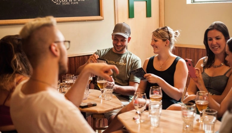 people laughing around a table at l'amère à boire - best brewpubs in montreal